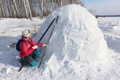 Happy woman skier in a red jacket sitting near an igloo. On a snowy glade, Siberia, Russia Stock Photo