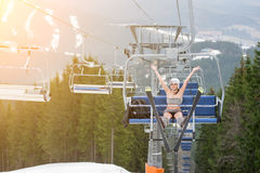 Happy woman skier is sitting on ski lift with skis, rising hand up and riding up to the top of the mountain Stock Photos