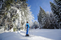 Happy woman skier on a ski slope in the forest Royalty Free Stock Image