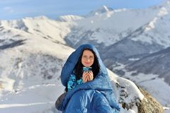 Happy woman in sleeping bag in snowy mountains royalty free stock image