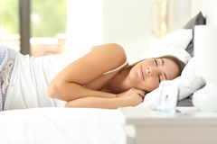 Happy woman sleeping deeply in a comfortable bed. In an hotel room or apartment royalty free stock image