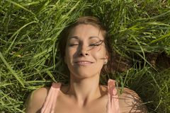Happy woman sleeping in meadow Stock Photos