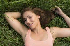 Happy woman sleeping in meadow Stock Photo