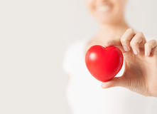 Happy woman with small red heart royalty free stock image