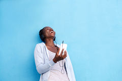 Happy woman with smart phone and headphones by blue wall Stock Images