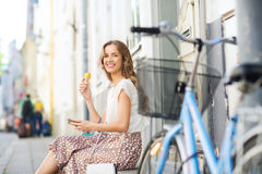 Happy woman with smartphone, bike and ice cream Stock Photo
