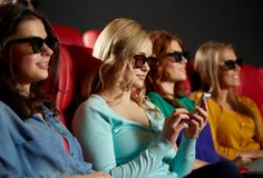 Happy woman with smartphone in 3d movie theater Royalty Free Stock Photography