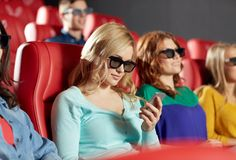 Happy woman with smartphone in 3d movie theater Royalty Free Stock Photos