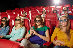 Happy woman with smartphone in 3d movie theater Royalty Free Stock Images