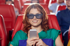 Happy woman with smartphone in 3d movie theater Stock Photos