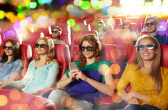 Happy woman with smartphone in 3d movie theater Stock Images