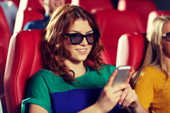Happy woman with smartphone in 3d movie theater royalty free stock image