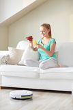 Happy woman with smartphone drinking tea at home Royalty Free Stock Photos