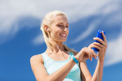 Happy woman with smartphone and earphones outdoors Stock Photos