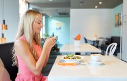 Happy woman with smartphone eating at restaurant Stock Photos