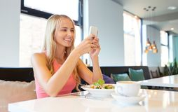 Happy woman with smartphone eating at restaurant Royalty Free Stock Photo