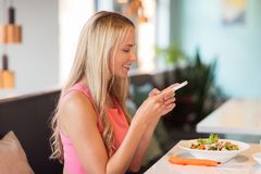 Happy woman with smartphone eating at restaurant. Eating, technology, communication and leisure concept - happy woman with smartphone and salad for lunch at royalty free stock photos