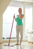 Happy woman with smartphone mopping floor at home Stock Images