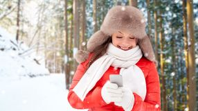 Happy woman with smartphone in winter stock image