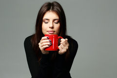 Happy woman smelling the aroma of coffee Stock Photo