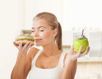 Happy woman smelling hamburger and holding apple Royalty Free Stock Image