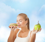 Happy woman smelling hamburger and holding apple Stock Image