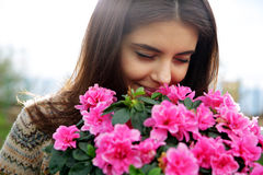 Happy woman smelling pink flowers Stock Images