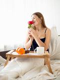Happy woman smelling rose while having breakfast in bed Royalty Free Stock Image