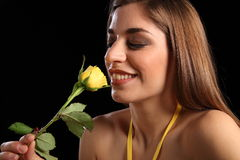 Happy woman smelling single yellow rose flower Stock Images