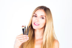 Happy woman with smile is holding cosmetic brushes. Make-up Royalty Free Stock Photos
