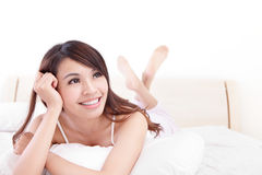 Happy woman smile while lying on the bed Stock Photography