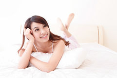 Happy woman smile while lying on the bed Royalty Free Stock Photography