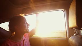 Happy woman smiles, enjoys traveling by car in summertime. Sunset rays. Slow motion sings song, 1920x1080. Happy woman enjoys traveling by car in summertime stock video footage