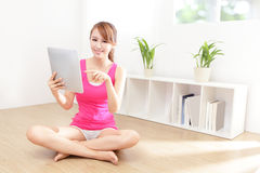 Happy woman smiles using tablet pc Stock Photography