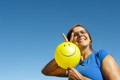 Happy woman with smiley balloon. An attractive looking woman in her fifties showing positive and optimistic attitude to life, smiling happily and holding a Royalty Free Stock Photo