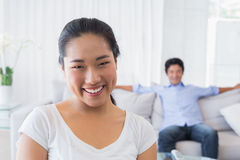 Happy woman smiling at camera with boyfriend in back Stock Photo