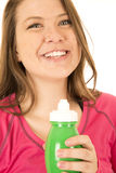 Happy woman smiling holding a green water bottle. Happy woman wearing a pink top smiling holding a green water bottle Royalty Free Stock Photo