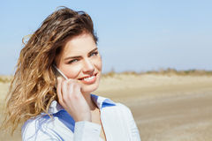 Happy woman smiling on the mobile phone Royalty Free Stock Image