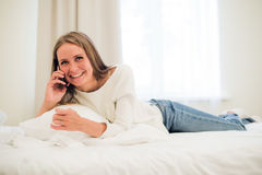 Happy woman smiling on the phone laying in bed.  Stock Photography