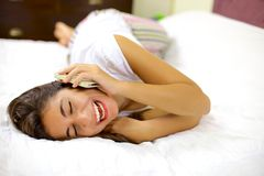 Happy woman smiling on the phone laying in bed. Cute young woman having fun in bed with cell phone Royalty Free Stock Photo