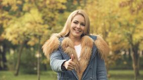 Happy woman smiling and showing thumbs up in autumn park, social insurance. Stock footage stock footage