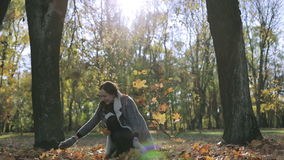 Happy woman smiling and throwing leaves in autumn. Brunette girl having fun playing in the park. The sun`s rays shimmer beautifully between trees stock video