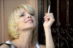 Happy woman smoking a cigarette Royalty Free Stock Images