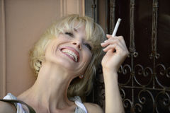 Happy woman smoking a cigarette Stock Photo