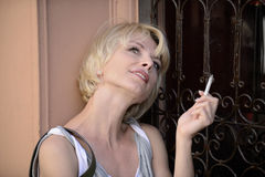Happy woman smoking a cigarette Royalty Free Stock Photography