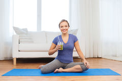 Happy woman with smoothie sitting on mat at home Royalty Free Stock Photo