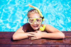 Happy woman with snorkel gear leaning on pool side Royalty Free Stock Image
