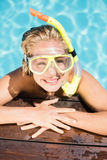 Happy woman with snorkel gear leaning on pool side Royalty Free Stock Photos