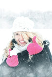 Happy woman in snow holding snow ball in hand for snowballing royalty free stock photo