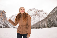 Happy woman with snowball outdoors among snow-capped mountains Stock Photos
